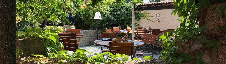 Der Biergarten bietet viele Plätze unter grünen Bäumen